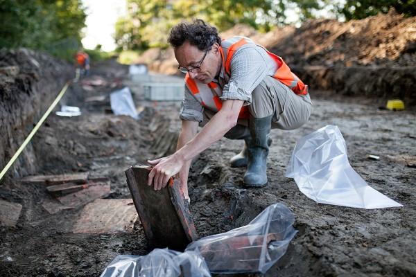 Een gevonden dakpann wordt door een archeoloog in Den Haag uit de grond getrokken. foto: gemeente Den Haag