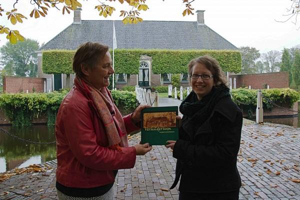 Schrijfster Jeanine Oostland (rechts) overhandigt het boek aan bestuurslid Anneke Sijpkens.