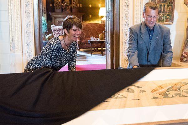 Pierre Cuypers, achterkleinzoon van Meesterarchitect Pierre Cuypers, onthult samen met gastconservator Barbara Laan de laatste ontwerptekening in de tentoonstelling 'Interieur & Lifestyle op De Haar' (foto: Anna van Kooij, via Kasteel de Haar)