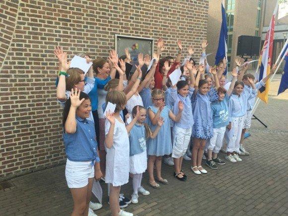 Minister Van Engelshoven (in het rood) gaat bijna verscholen achter het kinderkoor dat de bijeenkomst extra zonnig maakte
