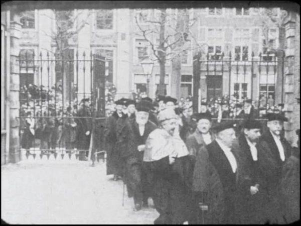 Albert Einstein draagt zijn toga van de universiteit van Berlijn met daarover de kappa van de universiteit van Madrid. Naast hem loopt Ehrenfest