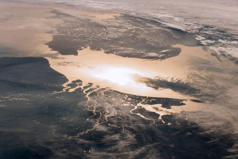 Nederland gezien vanuit het ruimtestation ISS. In de reflectie van het zonlicht tekent de rivierendelta zich scherp af tegen het donkere land