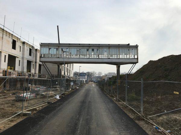De woningen worden momenteel gebouwd, rechts van de loopbrug komt het Bruggegebouw