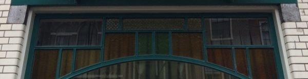Detail met bovenlichten van winkelpui Lange Mare 53. Naast het gekleurde glas zijn drie ruitjes met ventilatieglas zichtbaar