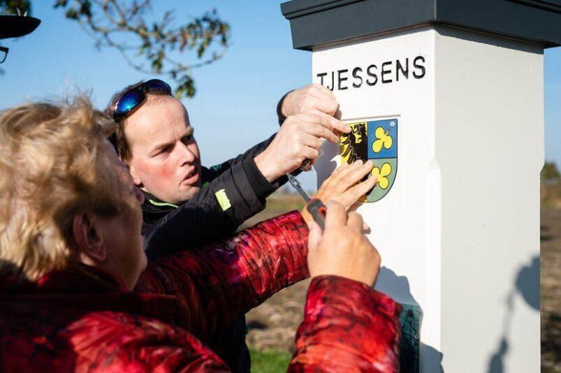 Wethouder Pytsje de Graaf bevestigt het bordje op een van de hekpalen van State Tjessens