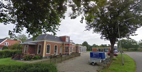 Het woonhuis met rechtsachter de werkplaats van de garage Warringa in Winsum