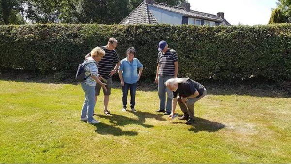 Arnold (tweede van links) bij het uitzetten van een putje van 1 bij 1 meter in een van de tuinen